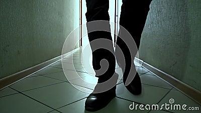 Homem em sapatos anda por um corredor sujo para frente na câmera, close-up video estoque