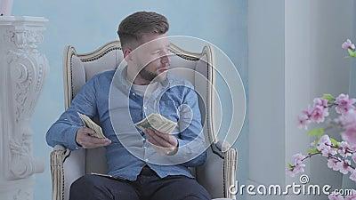 Homem farpado rico feliz na camisa azul que senta-se na poltrona branca na sala clara que conta o dinheiro Homem de neg?cios novo filme