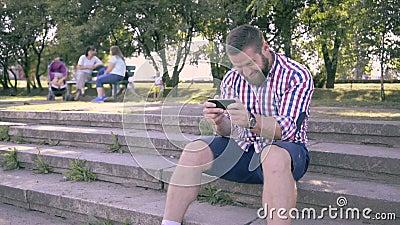 Homem feliz novo que joga jogos no smartphone no parque video estoque