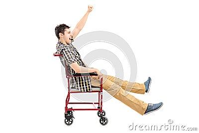 Homem feliz que senta-se em uma cadeira de rodas e em gesticular