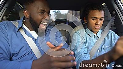 Homem feroz gritando em adolescente, filho aprendendo a dirigir carro, criando conflitos paternais video estoque