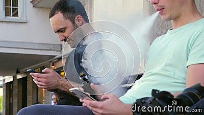 Homem fumando sinal eletrônico ao ar livre perto de outro cara filme