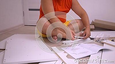 Homem gordinho agradável com barba em vestes amarelos coleciona móveis em casa usando Pensando sobre a instrução vídeos de arquivo