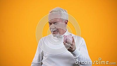 Homem idoso colocando moeda e cortando banco de porcos, poupança e orçamento, finanças filme