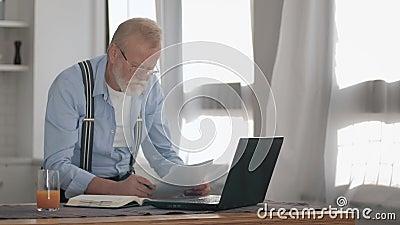 Homem idoso preocupado com barba cinzenta e óculos para obras de visão em laptop em casa estressado por causa filme