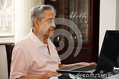 Homem idoso que usa o Internet