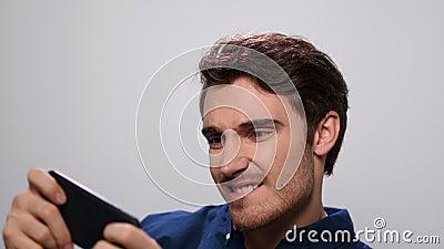 Homem jogando no smartphone no estúdio Paciente usando celular video estoque