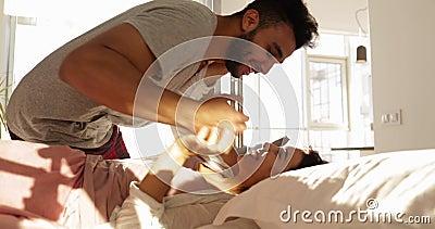 Homem latino-americano de sorriso feliz Carry Asian Woman To Bedroom, par romântico novo beijando na cama vídeos de arquivo