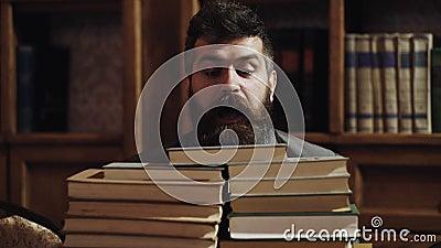 Homem, lerdo na cara surpreendida entre pilhas dos livros na biblioteca, estantes no fundo Professor ou estudante com barba filme