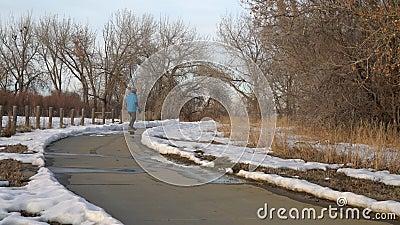 Homem maduro está viajando em um skate elétrico ao longo de uma trilha de bicicleta filme