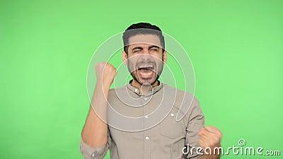 Homem-morena entusiasmado e entusiasmado com cerdas na camisa levantando seus punhos e gritando sim Eu sou vencedor, regozijando  vídeos de arquivo