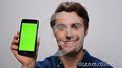 Homem mostrando smartphone com tela verde Homem mostrando telefone com chave cromática vídeos de arquivo