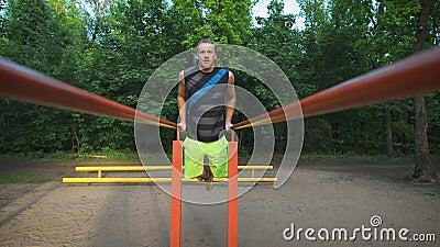 Homem muscular durante seu exercício no parque Mergulhos, caixa do exercício e tríceps filme