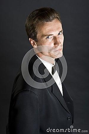 Homem no revestimento de jantar preto com laço de curva