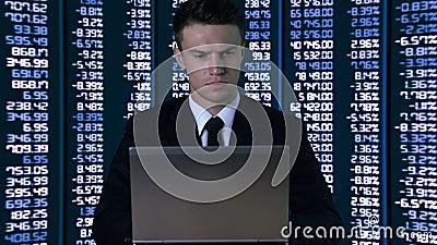 Homem no terno que texting no portátil contra o fundo em mudança dos dados numéricos vídeos de arquivo