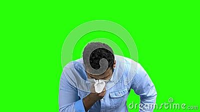 Homem novo aproximadamente a espirrar, tela verde filme