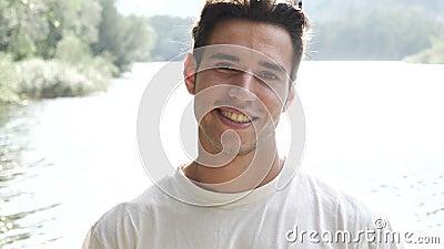 Homem novo considerável em uma costa ou em um rio do ` s do lago filme