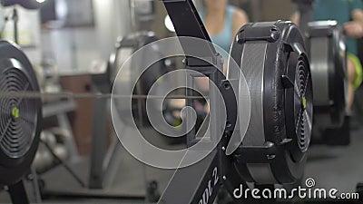Homem novo da aptid?o que usa a m?quina de enfileiramento no gym vídeos de arquivo