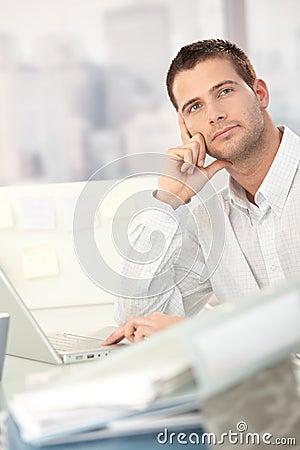 Homem novo Daydreaming que senta-se na mesa