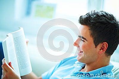 Homem novo de sorriso do handome que lê um livro