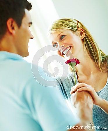 Homem novo feliz que entrega uma flor a uma mulher nova