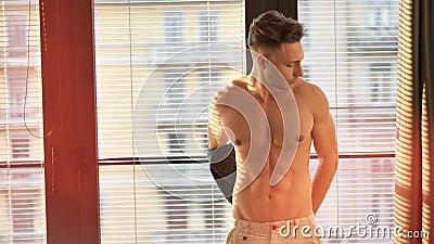 Homem novo muscular atrativo que despe-se em casa vídeos de arquivo