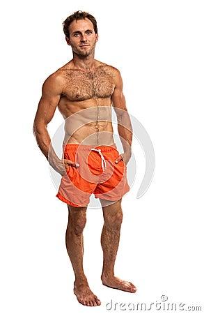 Homem novo muscular na posição do swimwear