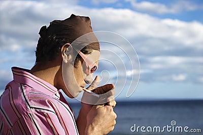 Homem novo na praia que ilumina um cigarro