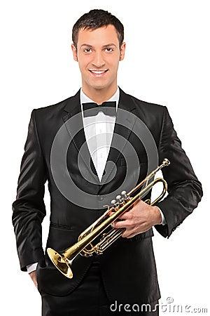 Homem novo no terno que prende uma trombeta