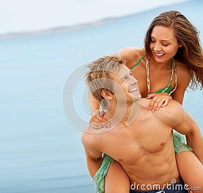 Homem novo que anda às cavalitas uma mulher bonita em uma praia