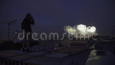 Homem novo que está no telhado da construção que toma a foto dos fogos-de-artifício na câmera filme