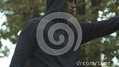 Homem novo que executa os pontapés, praticando nas artes marciais exteriores, maneira à saúde video estoque