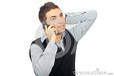 Homem novo que fala pelo móbil do telefone