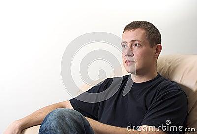 Homem novo que senta-se no sofá que presta atenção à tevê