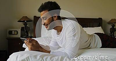 Homem novo que usa o tablet pc que encontra-se na manhã de sorriso feliz de Guy Chatting Online In Bedroom do hispânico da cama vídeos de arquivo