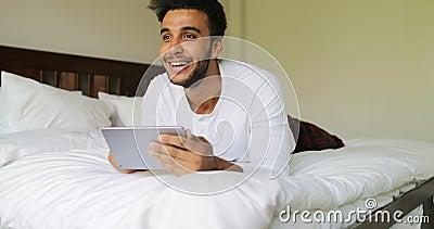 Homem novo que usa o tablet pc que encontra-se na manhã de sorriso feliz de Guy Chatting Online In Bedroom do hispânico da cama video estoque