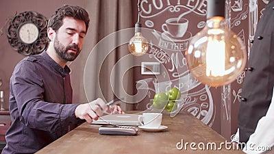 Homem novo que usa seu smartphone para fazer um pagamento em um contador e nas folhas da barra vídeos de arquivo