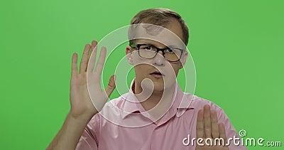 Homem novo tímido na camisa que acena suas mãos e que tenta pagar a atenção a ele filme