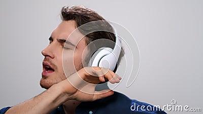 Homem ouvindo música nos fones de ouvido Guy dançando em fones de ouvido sobre fundo leve vídeos de arquivo