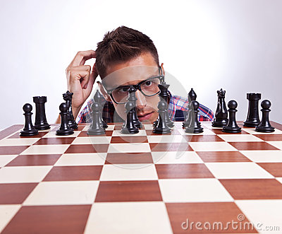 Homem pensativo na frente de seu primeiro movimento de xadrez