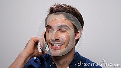 Homem positivo falando sobre smartphone em fundo de luz O cara ligando para o celular vídeos de arquivo