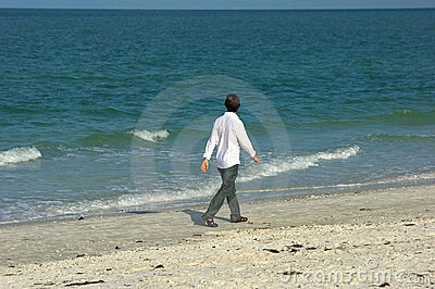 Homem que anda ao longo da praia