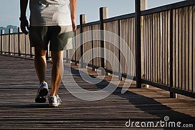Homem que anda no passeio à beira mar