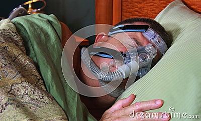Homem que dorme pacificamente com CPAP