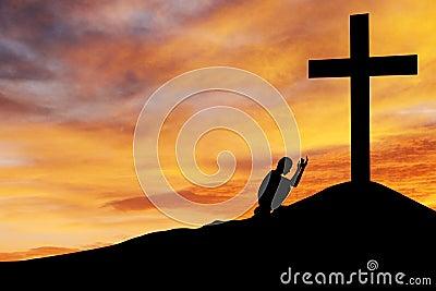 Homem que praying sob a cruz