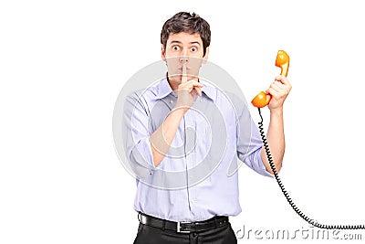 Homem que prende um telefone e que gesticula o silêncio