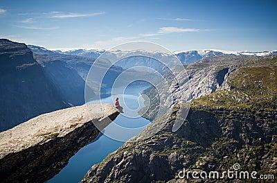 Homem que senta-se no trolltunga em Noruega