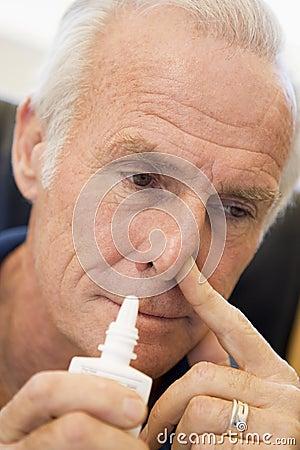 Homem sênior que usa o pulverizador nasal