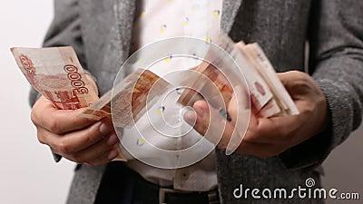 Homem sólido em fundo branco tem fã do dinheiro russo em suas mãos, conta video estoque