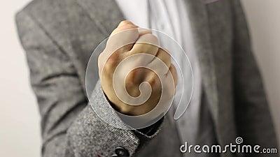 Homem sólido na jaqueta cinzenta sobre fundo branco puxando punho para cima. gesto de ameaça, conceito de agressão, aviso, puni filme